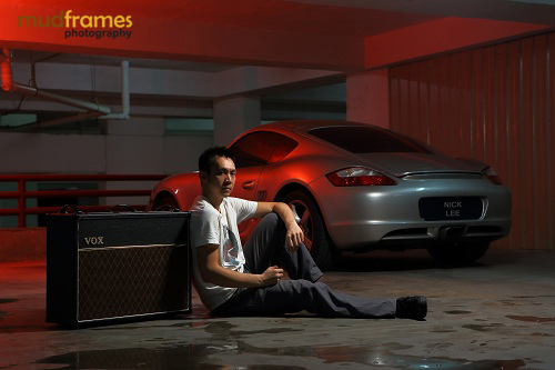 Test shot of Nick Lee in front of a Porsche at a basement car park