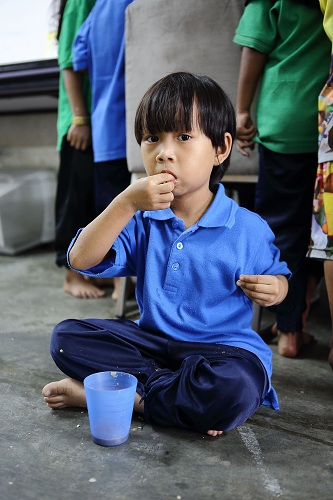 Myanmar child refugees having lunch at PBCC Learning Centre in Selayang
