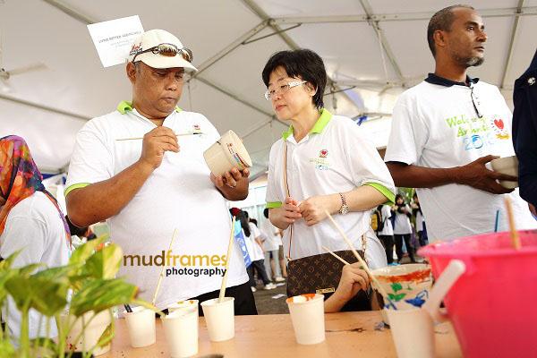 Dr. Jaafar bin Che Mat at Dr. Gun Suk Chyn painting flower pots at NCWO during World Arthritis Day 2013