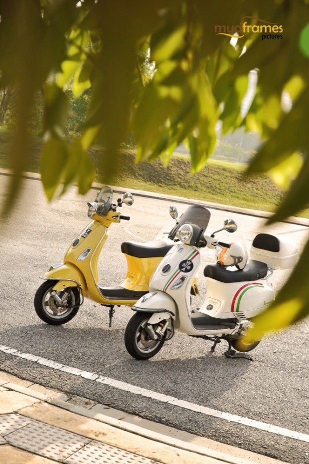 Two vespa scooters parked on the road side framed by foliages