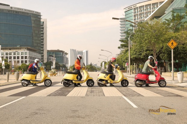 Vespa riders pushing their scooters across the road on a zebra crossing at Putrajaya