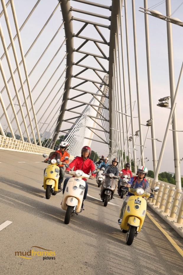 Vespa scooters passing the Putrajaya bridge
