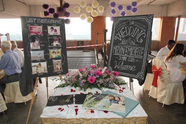 Chalkboard with lost childhood photographs on display on an easel during wedding